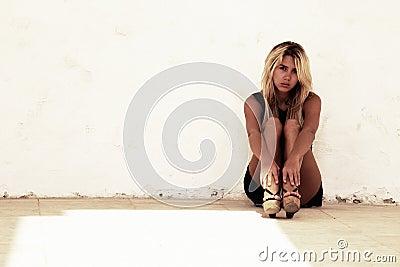 Adolescente sentado pela parede