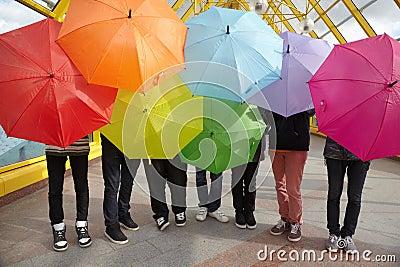 Adolescentes com os guarda-chuvas abertos na passagem superior do pedestre