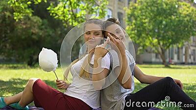 Adolescentes engraçados que sentam-se de volta à parte traseira e que enganam ao redor ao comer o algodão doce vídeos de arquivo