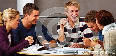 Adolescentes modernos - estudantes felizes que comem o alimento