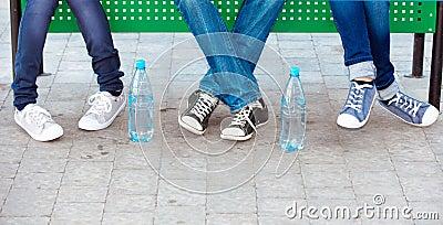 Adolescentes nas calças de brim e nas sapatilhas
