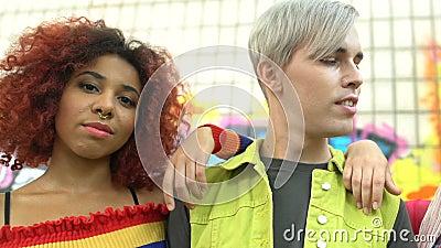 Adolescents branchés aux nez et oreilles percés posant devant la caméra, expression personnelle banque de vidéos