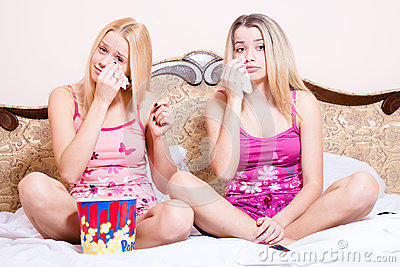 2 adorable attractive pretty young blond women sitting in bed with popcorn, watching movie and crying
