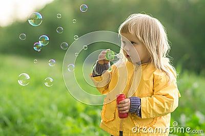 Adorable baby blow soap bubbles in park