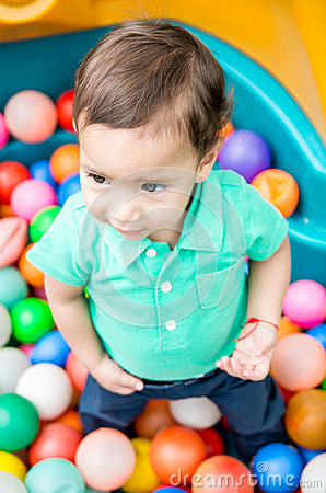 Free Adorable Baby Boy Wearing Turquoise T-shirt Playing With Colored Plastic Balls Shot From Above Angle Royalty Free Stock Photography - 71479087