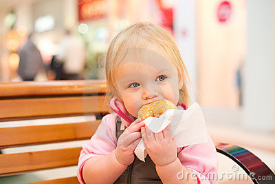 Adorable baby eat donut in mall