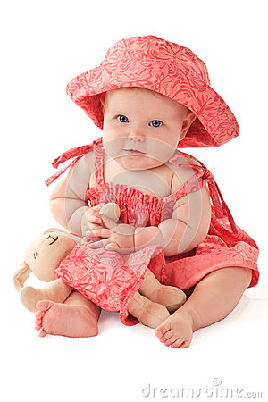 Adorable baby in pink dress plays with toy bunny