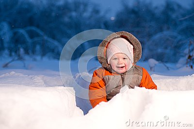 Adorable baby sit and digging hideout hole in snow