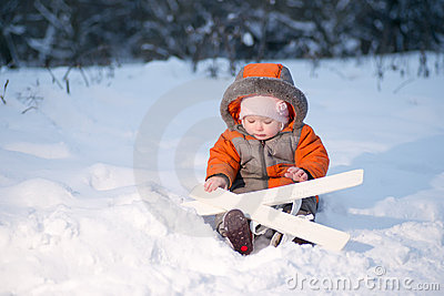 Adorable baby sit on snow with ski