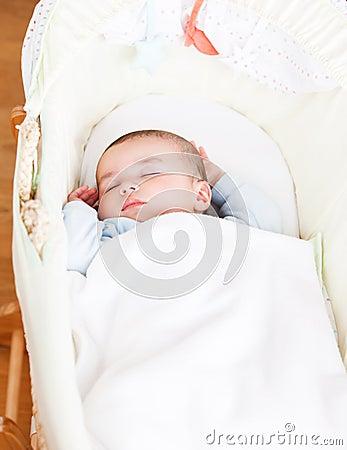 Adorable baby sleeping in his cradle