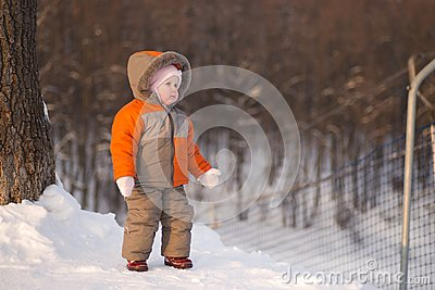 Adorable baby stay near ski protection fence