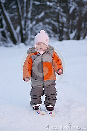 Adorable baby walk on ski in park