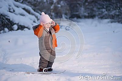 Adorable baby walk on ski in park