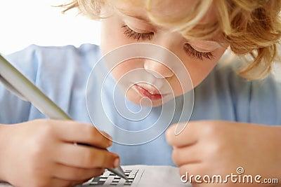 Adorable boy holding pen while solving puzzle