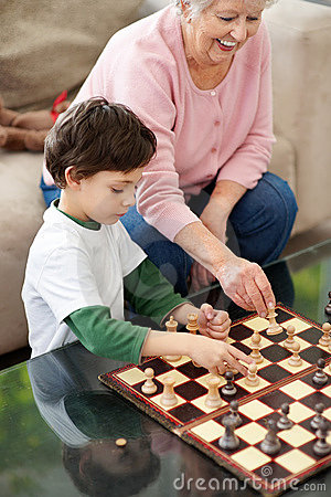 Adorable boy playing chess with his grandmother