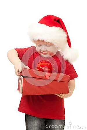 Adorable boy in Santa hat opening christmas gift