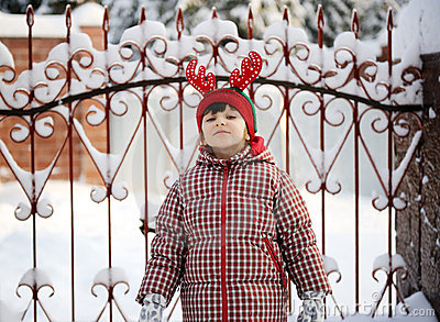 Adorable child girl in horned hat poses outdoors