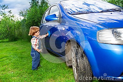 Adorable child helping to wash car