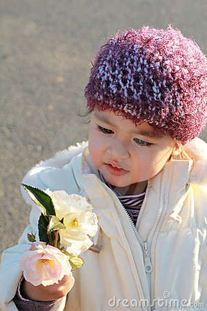 Adorable child  looking at flowers