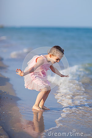 Adorable child playing at the beach
