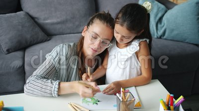 Adorable child and woman drawing picture at home enjoying art and leisure time. Adorable child and pretty young woman are drawing picture at home enjoying art stock footage