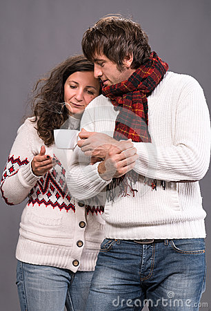 Adorable couple holding cup of coffee