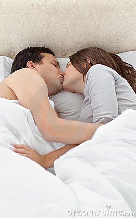 Adorable couple kissing while relaxing on the bed