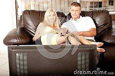 Adorable couple watching tv