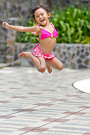 Adorable ethnic child in swimsuit jump high