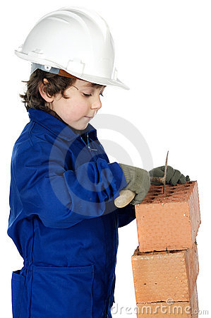 Adorable future builder constructing a brick wall