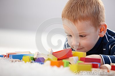 Adorable ginger-haired boy playing with cubes