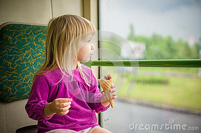 Adorable girl eat ice cream riding bus
