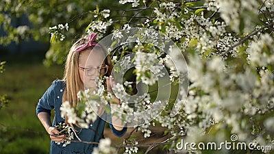 Adorable girl enjoying smell of spring garden stock footage