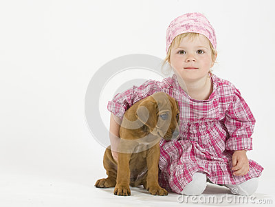 Adorable girl is hugging her puppy