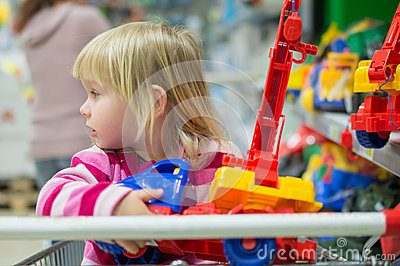 Adorable girl look to toys sit in shopping cart