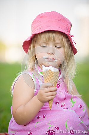 Adorable girl in pink hat eat ice cream