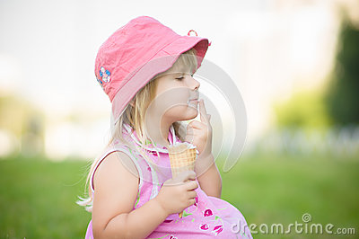 Adorable girl in pink hat eat ice cream on grass