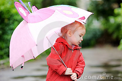 Adorable girl at rainy day in autumn