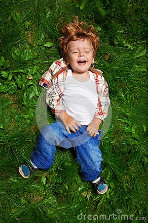 Adorable kid laughing on grass