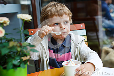 Adorable little boy eating frozen yoghurt ice cream in cafe