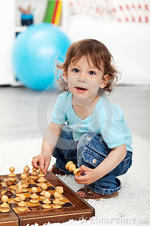 Adorable little boy playing with chess pieces