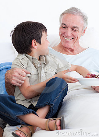 Adorable little boy taking care of his grandfather