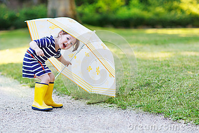 Adorable little child in yellow rain boots and umbrella in summe