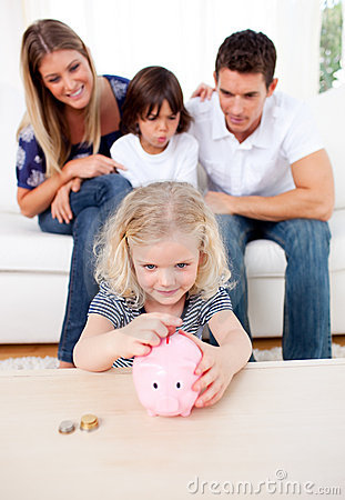 Adorable little girl inserting coin in a piggybank