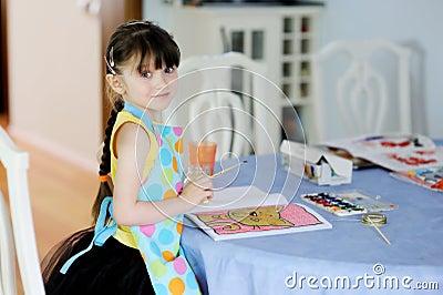 Adorable little girl with long dark hair draws