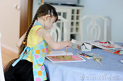Adorable little girl with long dark hair draws