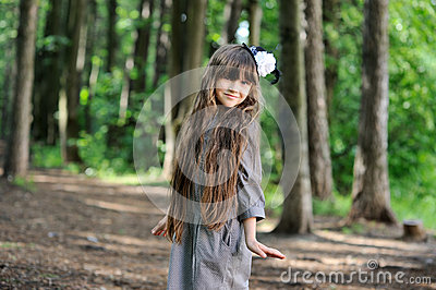 Adorable little girl posing in summer forest