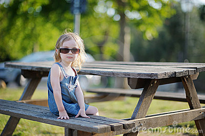 Adorable little girl sitting on a bench