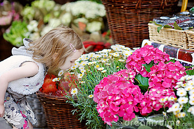 Adorable little girl smelling flowers
