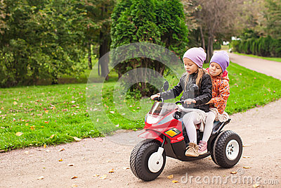 Adorable little girls riding on kid s motobike in